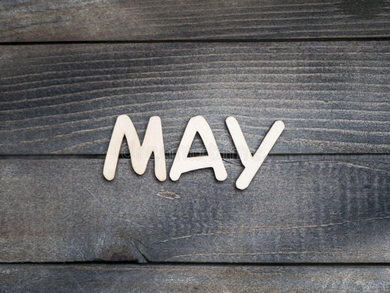 Nazwa miesiąca składa się z jasnych drewnianych liter na ciemnym drewnie Maj obrazy stock