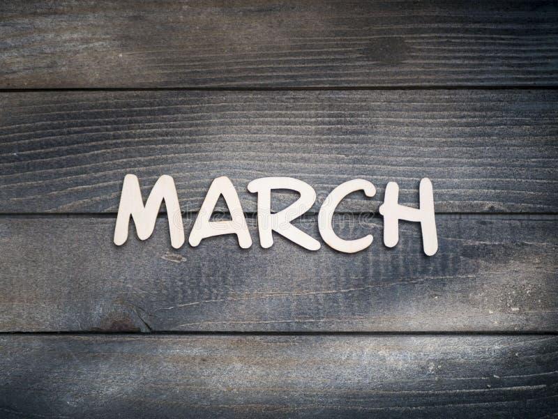 Nazwa miesiąca składa się z jasnych drewnianych liter na ciemnym drewnie Marzec zdjęcie royalty free