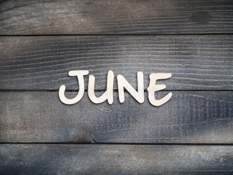 Nazwa miesiąca składa się z jasnych drewnianych liter na ciemnym drewnie Miesiąc czerwca fotografia stock