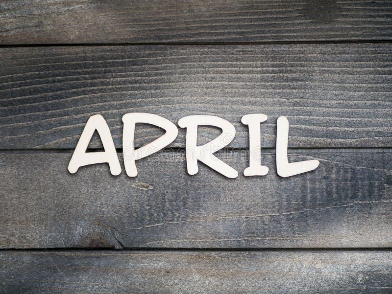 Nazwa miesiąca składa się z jasnych drewnianych liter na ciemnym drewnie Miesiąc kwietnia obrazy royalty free