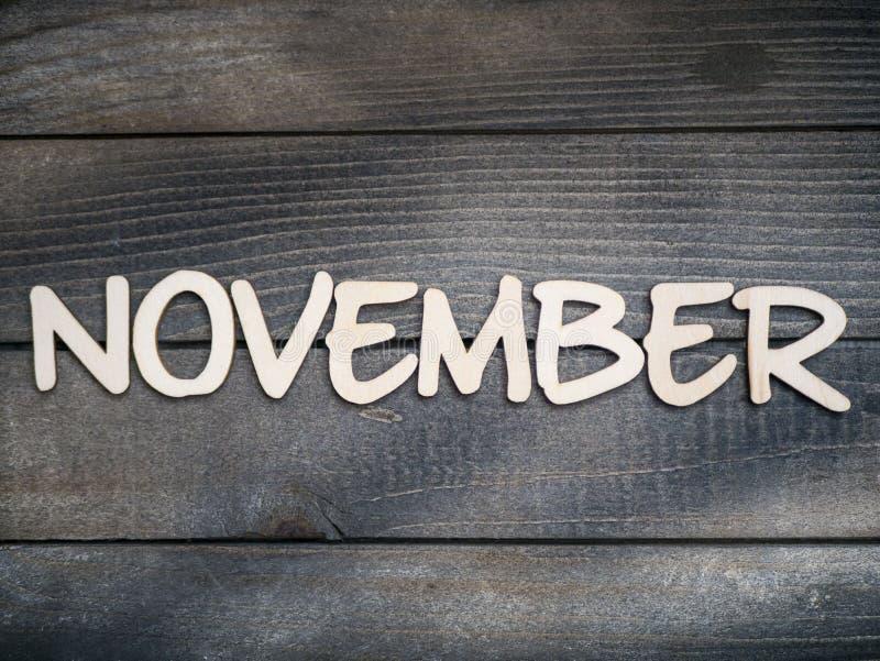 Nazwa miesiąca składa się z jasnych drewnianych liter na ciemnym drewnie Miesiąc listopada obrazy royalty free