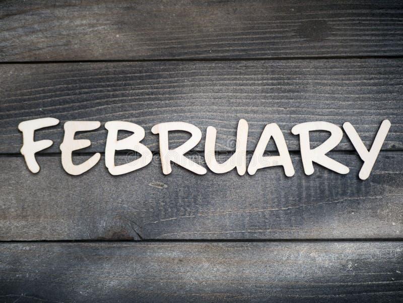Nazwa miesiąca składa się z jasnych drewnianych liter na ciemnym drewnie Miesiąc lutego obraz stock