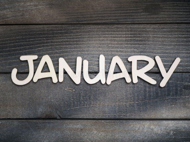 Nazwa miesiąca składa się z jasnych drewnianych liter na ciemnym drewnie Miesiąc stycznia zdjęcia royalty free