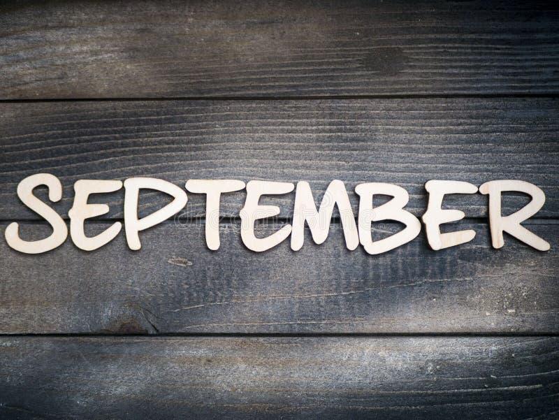Nazwa miesiąca składa się z jasnych drewnianych liter na ciemnym drewnie Miesiąc września obraz stock