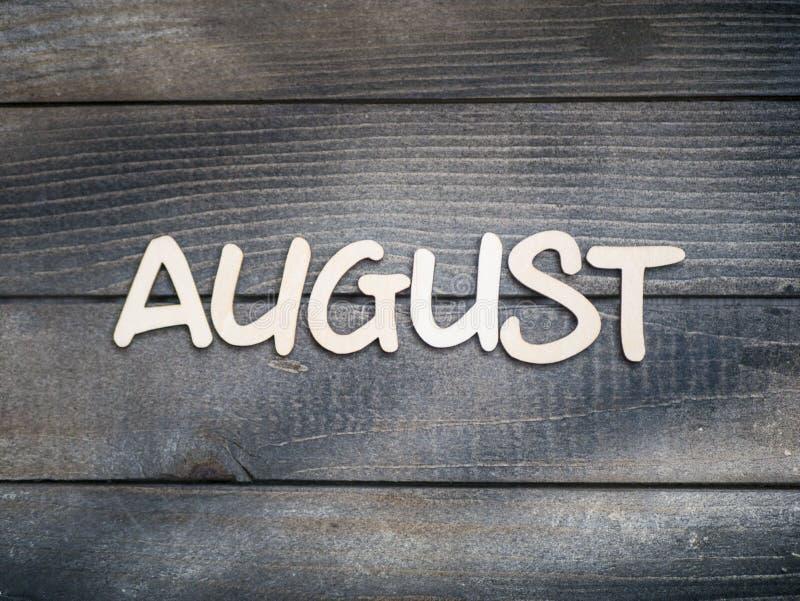 Nazwa miesiąca składa się z jasnych drewnianych liter na ciemnym drewnie Sierpień zdjęcia royalty free