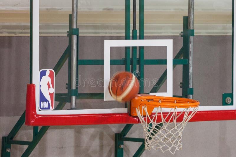 NBA-logo på en målbräda, medan en basket ska just att göra poäng på dess cirkel arkivbilder