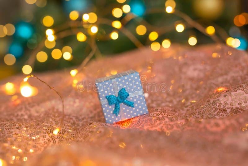 NBlue-Geschenk auf einem korallenroten Hintergrund gegen einen unscharfen Baum des neuen Jahres verziert mit Gold und blauen Bäll stockbild
