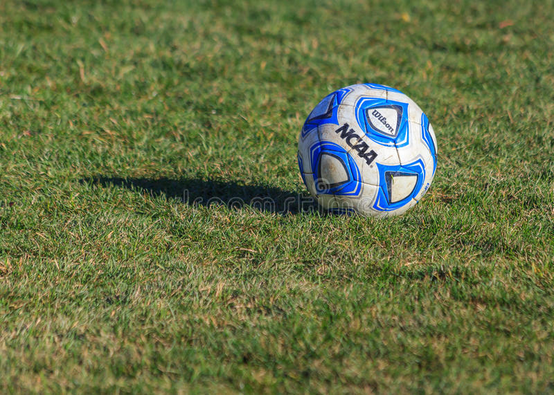 NCAA College Soccer Ball on Grass Field. NCAA college soccer ball, blue, white and black, on grass field royalty free stock images