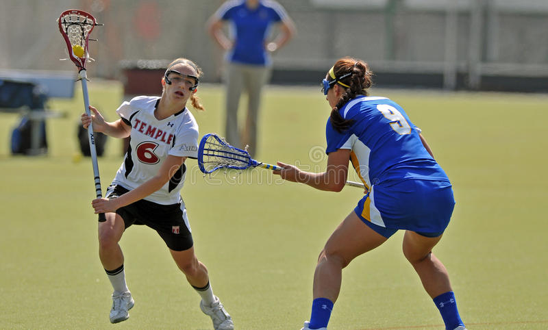 NCAA Women's Lacrosse (LAX). PHILADELPHIA - MARCH 17: Temple women's lacrosse player Charlotte Swavola (#6) tries to avoid a check by Delaware's Alex Alois (#9) royalty free stock image