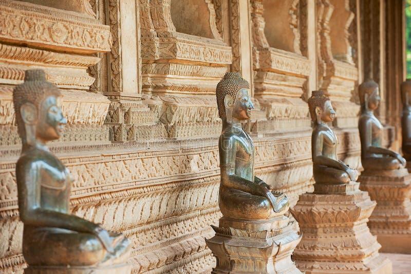 Ncient reveste as estátuas da Buda situadas fora do templo anterior do templo de Hor Phra Keo de Emerald Buddha em Vientiane, Lao imagem de stock royalty free