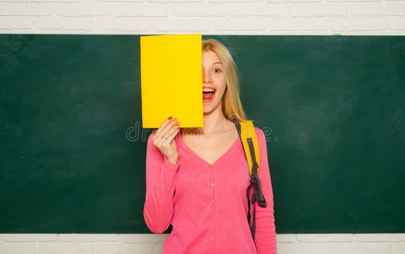 An?ncio feliz da terra arrendada da menina quando suporte na sala de aula Estudante com trouxa Educa??o escolar alta grande foto de stock royalty free