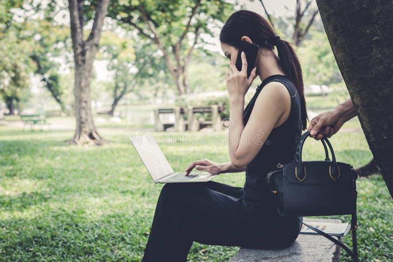 Nd do ladrão que pegara o saco atrás da mulher, que se senta e se fala com o amigo no smartphone no jardim conceito do bandido cr fotos de stock