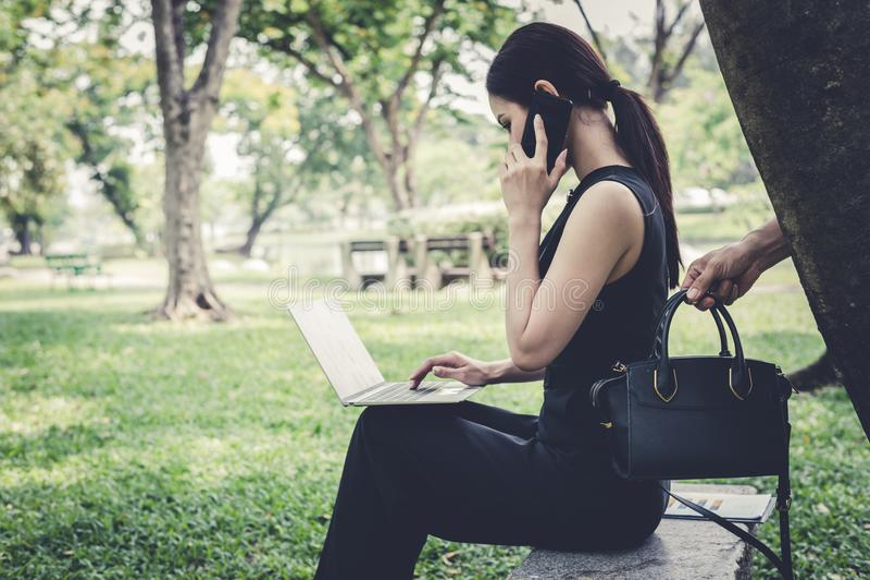 Nd podnosi w górę torby za kobietą złodziej, który siedzi i opowiada z przyjacielem na smartphone przy ogródem pojęcie kryminalny zdjęcia stock