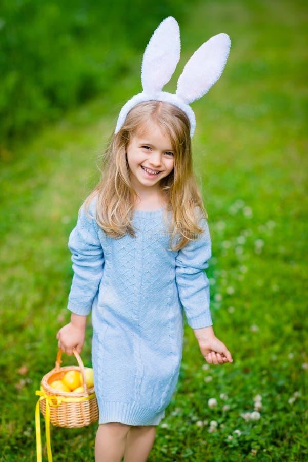 Nd sonriente de los oídos del conejito de la niña que lleva que sostiene la cesta de mimbre con los huevos amarillos fotos de archivo