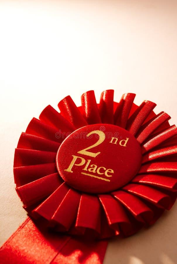 2nd ställevinnarerosett eller emblem i rött fotografering för bildbyråer