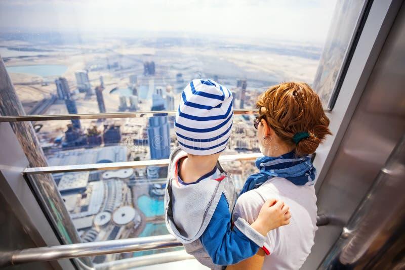 ND suo figlio del bambino che esamina dalla finestra, mentre visitando la piattaforma di osservazione superiora fotografia stock