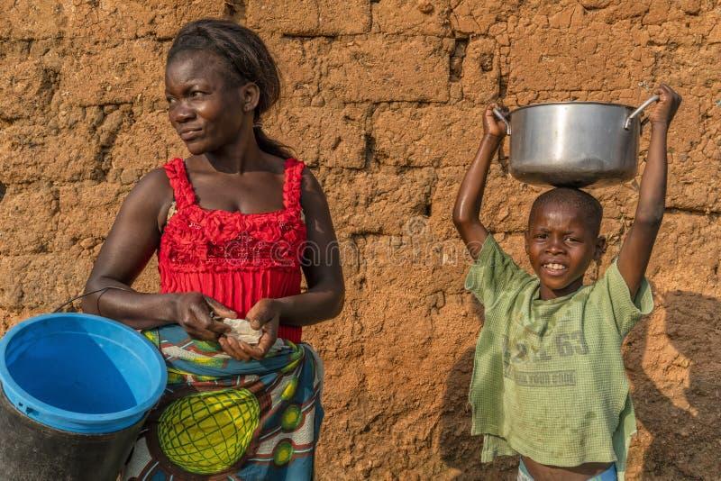NDALATANDO/ANGOLA - 27 de julio de 2017 - madre e hijo africanos en pueblo en África rural con loza foto de archivo