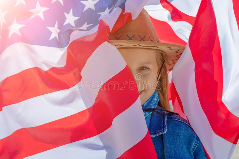 Ndependence Day. Beautiful happy girl with green eyes on the background of the American flag on a bright sunny day. A girl in a stock image