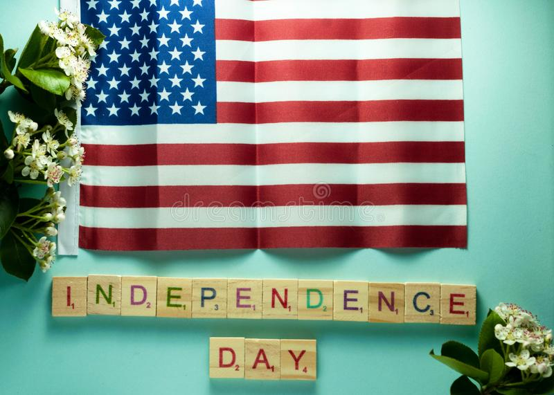 Ndependence day lettering on wooden cubes under American flag royalty free stock photo