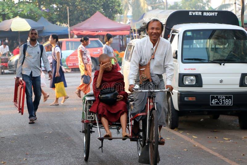 Neófito de Myanmarese del monje que se sienta en el taxi del triciclo de la bicicleta con el montar a caballo del conductor en el foto de archivo