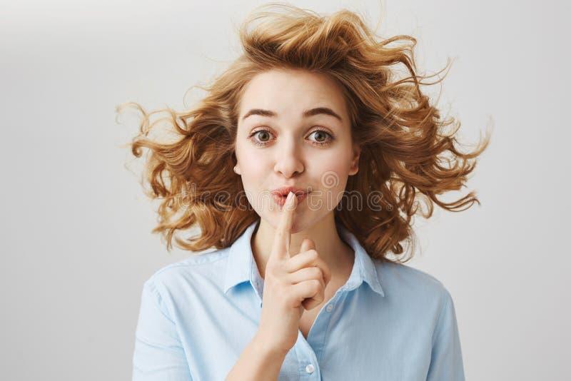 Ne dites pas n'importe qui au sujet de notre petit secret Femme optimiste attirante de portrait avec la coupe de cheveux bouclée  images libres de droits