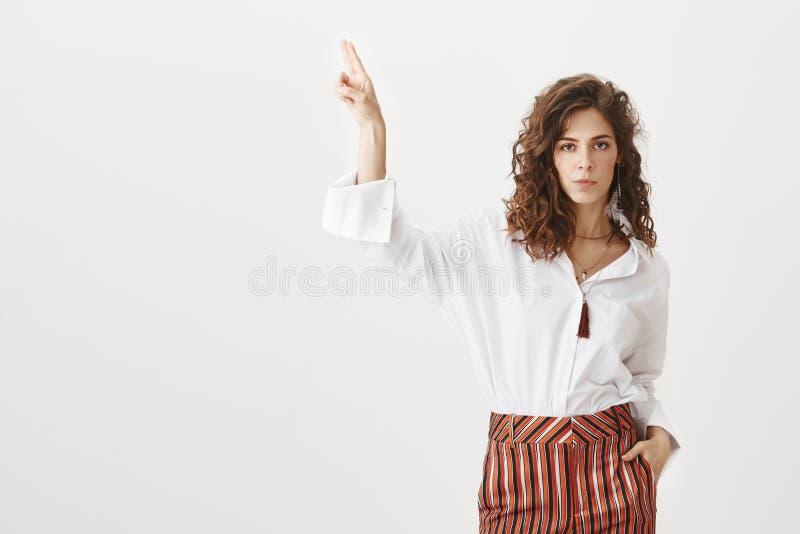 Ne dites pas plus, regardez là Femelle belle calme et sérieuse sûre dans des pantalons rayés, tenant la main dans la poche photographie stock