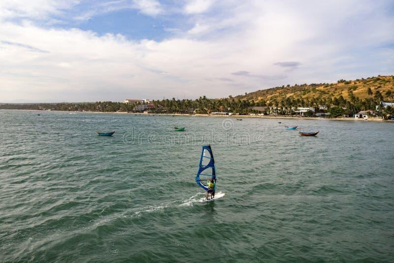 Ne Mui, Вьетнам Спорт ветра игры человека занимаясь серфингом в море под обширным голубым небом стоковые фото