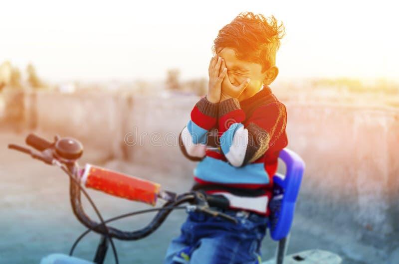 Ne regardez pas le garçon -timide sur la bicyclette photographie stock