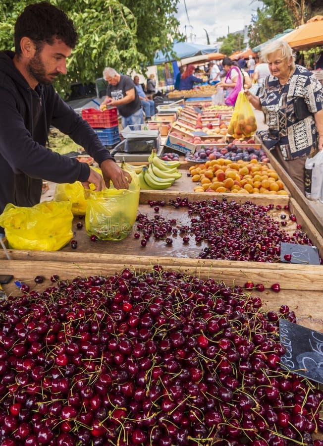 Nea Artaki Evia ö, Grekland Juli 2019: Grekisk bymarknad på ön av Evia med körsbäret, frukter och grönsaker på en sol arkivbild