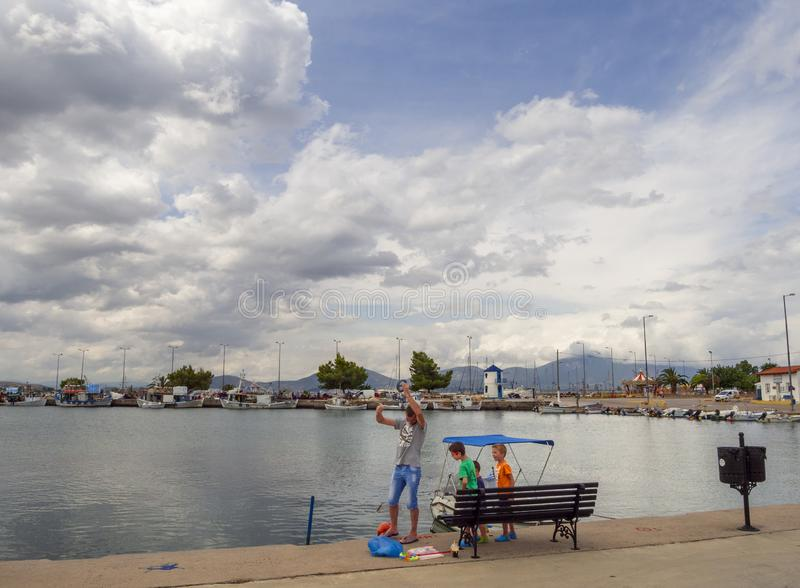 Nea Artaki, Evia island, Greece. July 2019: Fisherman with children fishing on the waterfront on a sunny afternoon on the calm Aeg stock photography