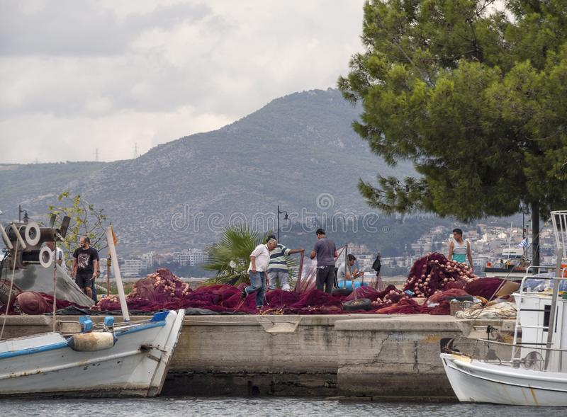 Nea Artaki, Evia island, Greece. July 2019: Fishermen mend fishing nets on the waterfront in Fishing boat on a sunny afternoon on stock photography