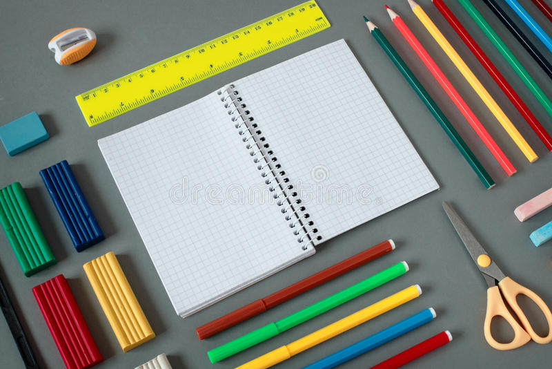 Nealty Organized Colorful School Supplies on Desk. High Angle View of Colorful School Supplies Organized by Type Around Note Book Open to Blank Page Arranged on stock photo