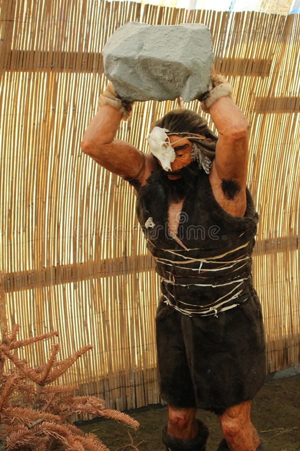 Neanderthaler mens met grote steen boven hoofd stock fotografie