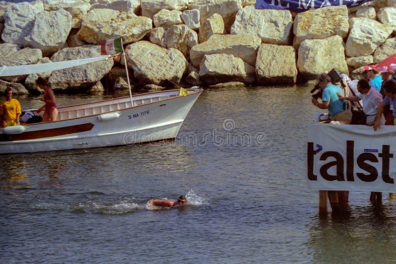 NEAPEL, ITALIEN, 1988 - der Sieger Capris-Napoli Querfeldeinmarathon schwimmend gibt die Schlussstriche vor Ankunft lizenzfreies stockfoto