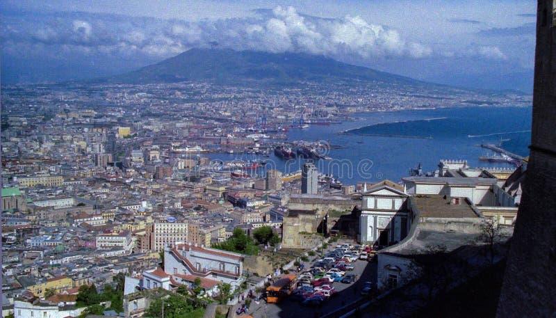 NEAPEL, ITALIEN, 1986 - die Mitte und der Hafen von Neapel gesehen von Castel S Elmo mit Vesuv, der unter den Wolken sich verstec lizenzfreie stockfotografie