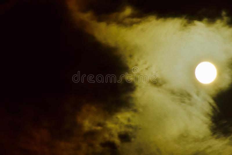 The bright moon shining through the clouds. A near full moon embedded in the clouds brightens the night sky royalty free stock image