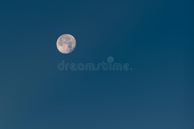 Near Full Moon with Visible Craters in Blue Winter Sky royalty free stock photos