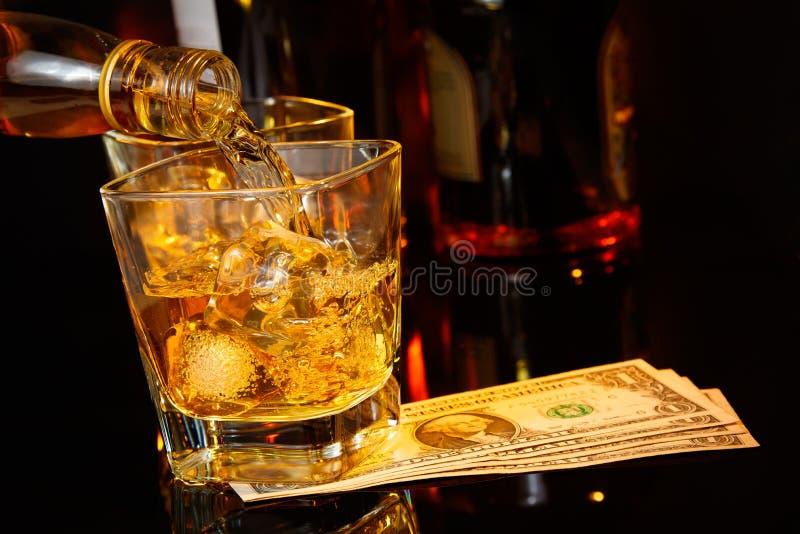 Near hällande whisky för bartendern framme av whiskyexponeringsglas och flaskor dollar fotografering för bildbyråer