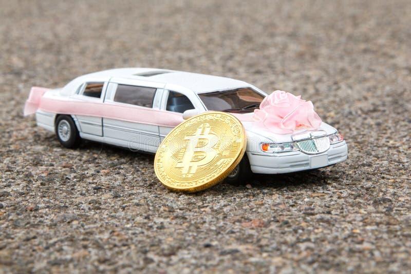Near modell Bitcoin för guld- mynt av den lyxiga långa vita bilen på asfaltbakgrund Bröllop Bitcoin accepterade och finansiellt arkivfoto