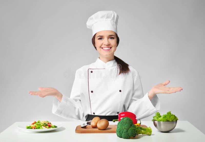 Near tabell för kvinnlig kock med produkter fotografering för bildbyråer