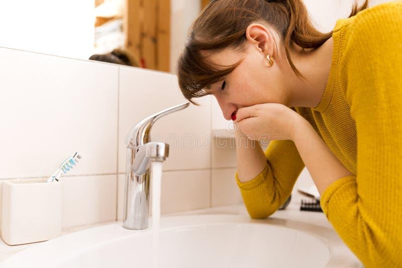 Near vask för ung spykvinna i badrum arkivbild