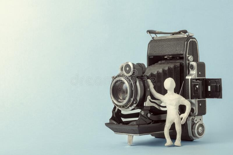 Near the vintage camera stands a man of white plasticine. Copy space royalty free stock image