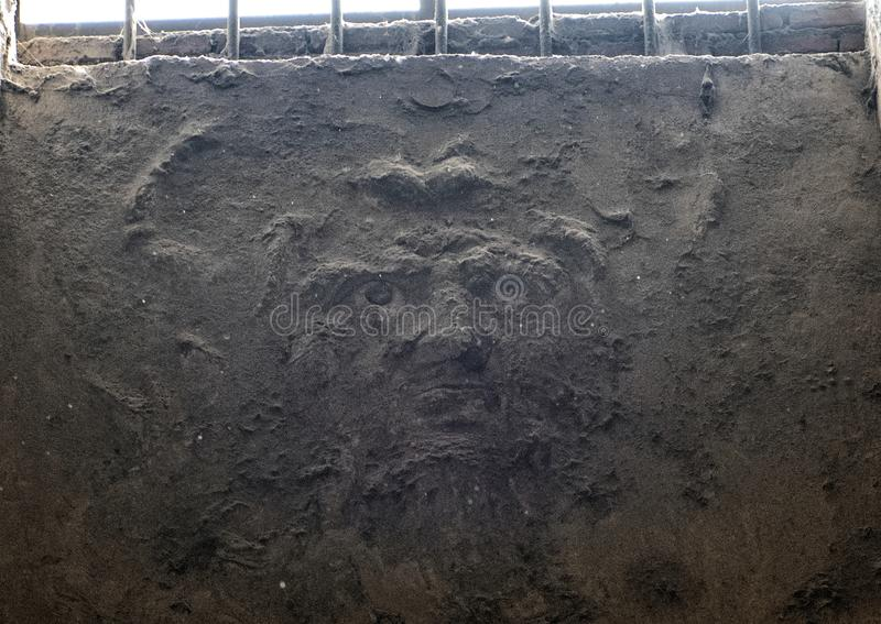 Nearly hidden face inner wall Roman bath, Scavi Di Pompei. Pictured is a nearly hidden face on an inner wall of a bath in the Scavi Di Pompei. The archaeological royalty free stock photo