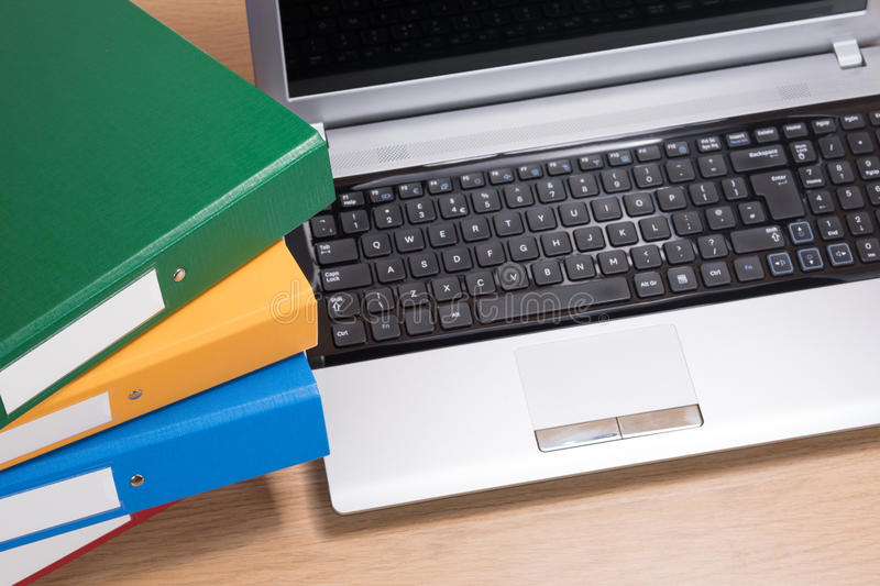 Neat office desk with laptop and stacked folders stock photos