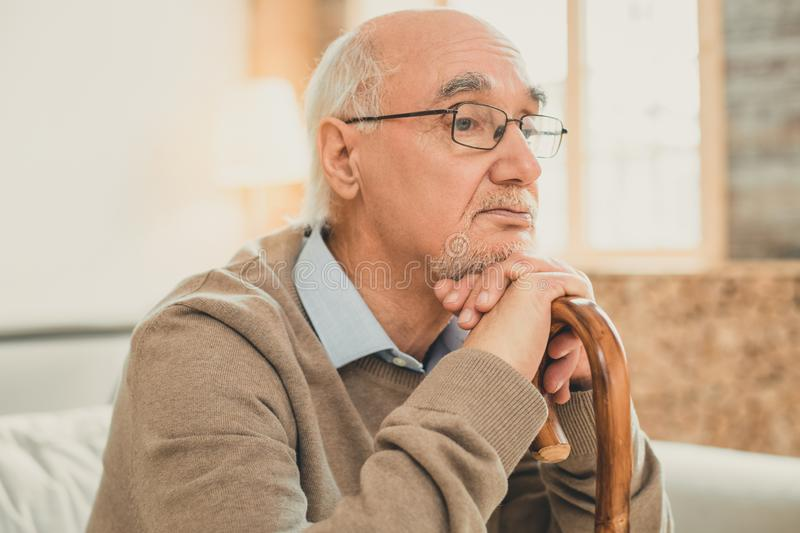 Neat partly-bald old man thoughtfully relying on the wooden stick. Bored face. Neat partly-bald old man thoughtfully relying on the wooden stick while spending stock image