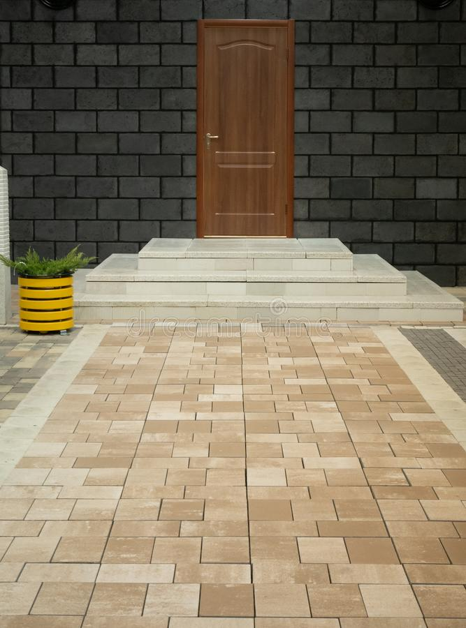 Neat pavement porch made of stone tiles leading to modern house entrance door with few marble steps and cute yellow flower pot. stock images