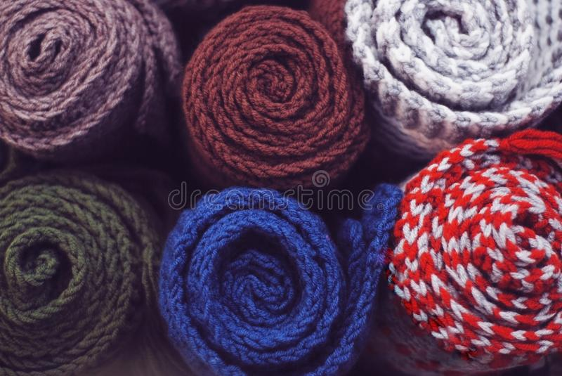 A neat pile of rolled knitted warm blankets. Comfort, warmth and a homely atmosphere in the cold winter. Vintage styled royalty free stock photo
