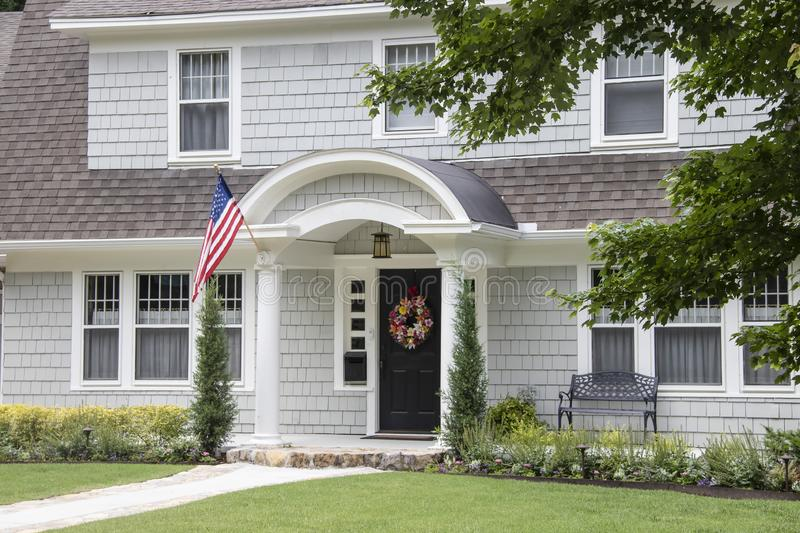 Neat and pretty shingled retro house with arched entryway and beautiful landscaping with colorful summer wreath on front door and. American Flag attached to stock images