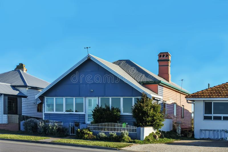 Neat and tidy houses beside highway in suburban Brisbane in Australia`s typical bright sunshine with metal and tile roofs.  stock images