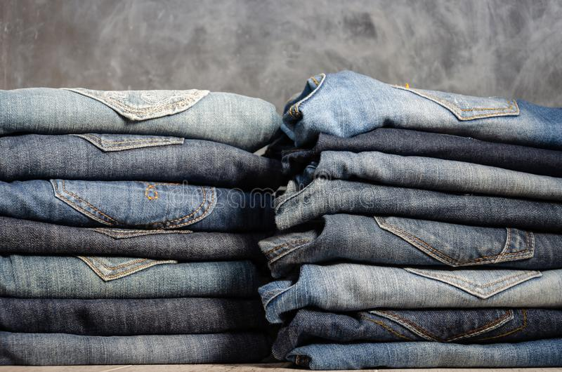Neatly folded jeans in two piles on a gray background. Close-up of jeans in different colors. Denim background royalty free stock photography
